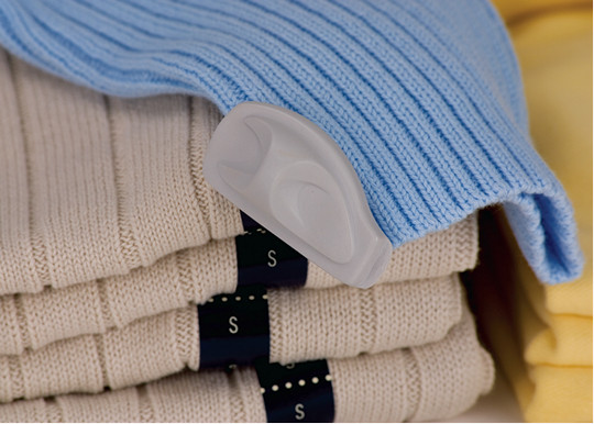 Sensormatic Visual Source Tag applied to a stack of sweaters